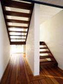 moderne, schlichte Holzwangentreppe als gegenläufige Podesttreppe in Mahagoni 1A natur lackiert.