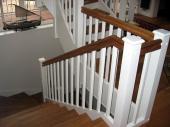 Treppenbelegung in Eiche 1A geölt mit weißen Wangenverkleidungen und eckigen Geländerstäben, Handläufe in Eiche 1A geölt mit Omega-Profil, klassische Pfosten mit Dach